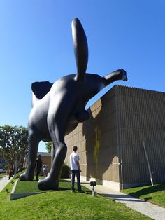 A passer-by looks at Richard Jackson's giant installation of a dog relieving itself on the Orange County Museum of Art in Newport Beach, California. The 28ft tall and 33ft long steel structure  - dubbed Bad Dog - has been rigged to spray yellow paint onto the side of the museum.
