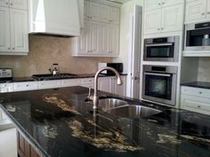 Titanium Granite is perfect dark granite. Its movement with creams and whites is great for a white kitchen.