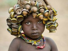 """French photographer Eric Lafforgue (b.1964) """"has spent several years exploring the customs of an Ethiopian semi-nomadic tribe known as 'The Daasanach', a group made up of some 50,000 individuals who re-appropriate discarded objects and manufactured goods. Using bottle caps, hair clips and old wristwatches the women turn these items into beautiful head wear and jewelry, designed to be worn by young and old."""" via junkculture"""