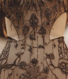 A detail of the back of the Magical Map dress shows ancient keys, all hand-embroidered with a combination of beads, glass stones and silk and feather fringes.