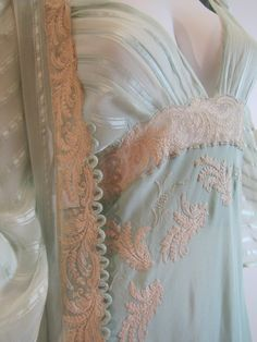 Unknown designer 1930s French. Pastel Aqua nightgown and robe with French braided shoulder straps and a French made needle run lace band across the bodice. The robe is sheer aqua silk crepe accompanied by finely woven silk ribbon stripes. Silk covered buttons down the front bodice, and more French lace for the trimming. Hand stitched. *vintage leavers*