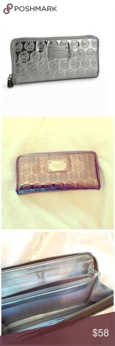"""MICHAEL KORS JET SET WALLET Jet Set logo. Steel/ silver metallic color. The only imperfections I see is on the zipper tab and just a minor scratch on face plate. Zoom in on pics and check it out. Photo one is stock. 8"""" x 4"""" holds an iPhone 6/7 plus fine Michael Kors Bags Wallets"""
