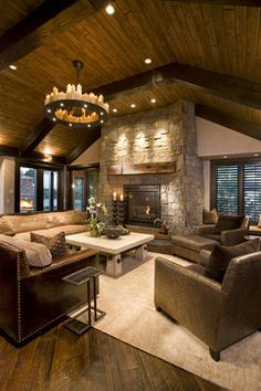 A rustic traditional living room features a trio of espresso leather arm chairs, a huge flagstone fireplace, a square coffee table and a large brown sofa