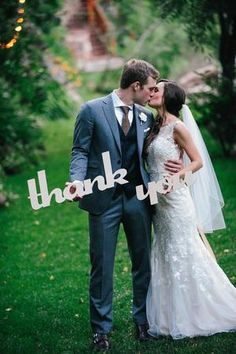 Bride and groom kissing while holding cut out thank you signs @myweddingdotcom