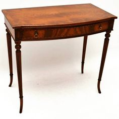 Antique Regency Style Mahogany Console / Side Table at Marylebone Antiques | Elegant antique Regency style mahogany side table with a single bow fronted drawer with an inlaid edge. The top is flame mahogany with a cross banded top edge & a reeded front. The flame mahogany drawer has fine dovetails & original brass handles. This table sits on elegant turned fluted legs with kick out feet. It's in excellent condition with plenty of character & dates from around the 1920's period. Contact us at…