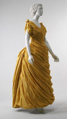 This early 1880s evening gown, attributed to Liberty of London, shows the heavy influence of the Victorian Aesthetic movement on fashion