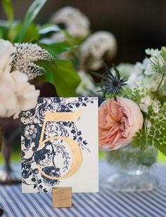 A navy floral print table number with gold typography, a striped tablecloth and blush and white peony centerpieces for a spring wedding table.