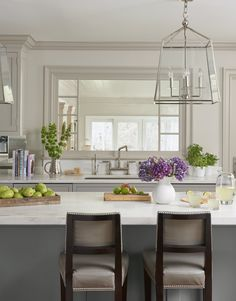 Large lantern-style chandeliers over a marble-topped island add sophistication to this remodeled 1970s kitchen.