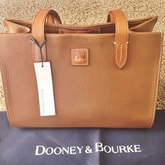 Dooney & Bourke Tote Beautiful tan color tote from Dooney & Bourke. Bought and wore for a week when I traveled to TX. In near perfect condition. Only minor flaw is the cracking inside the leather strap but it's very minor and unnoticeable when worn. I just don't want anyone to have any surprises when they get it. Of course it's 100% authentic and it comes with its tags, dust bag, and registration card ❤️ Dooney & Bourke Bags Totes