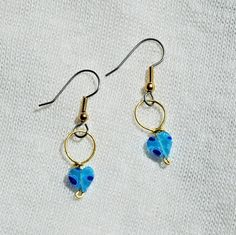 This is a pair of wire-wrapped earrings made with brass wire and featuring pretty blue heart beads.