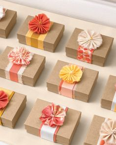 Do guests a favor and present them with a small gift planted inside these petite flower-topped boxes. Wrap each small box with a belt of layered ribbons or a strip of woven fabric, and cap it off with a single fabric blossom.
