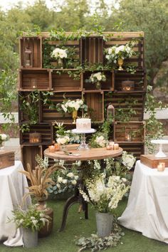"Can a beautiful backdrop be as easy as just placing vases of flowers at different heights? Sure! This rustic crate setup allows you to just place a number of arrangements in the ""cubbies"", no taping, cutting, or gluing required."