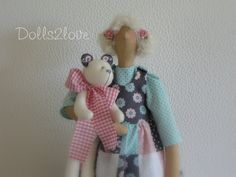 Tilda doll Rosemay wearing a mint green, soft pink and anthracite patchwork pinafore dress accompanied by her little teddy bear made by Dolls2love on Etsy, €49.50.