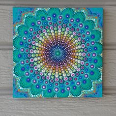Spring Mandala 10 inch by 10 inch Wood Canvas, Ready to Hang  This Mandala begins with a beautiful turquoise background. A touch of spring green blooms from the center unfurling all the magnificent colors of spring. From the shades of Crocuss to Sunflowers this Mandala truly blooms. Painted with acrylic paints on wood. Ready to hang with a sawtooth hanger already attached to the back. Original Art by Kaila Lance. A non toxic protective clear coat has been applied to this painting. The sides…