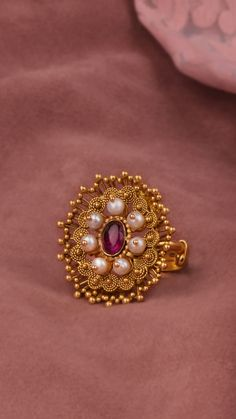 Granules of gold and pearls around a vibrant centre on the AZVA ring. Gold Jhumka Earrings, Jewelry Design Earrings, Gold Earrings Designs, Gold Jewellery Design, Gold Jewelry Simple, Gold Rings Jewelry, Hand Jewelry, Gold Finger Rings, Gold Ring Designs