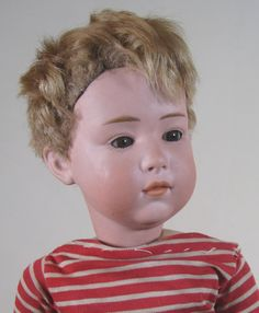 """11"""" bisque pouty faced boy doll, head mold no. 6970, glass inset eyes, with original clothing and wig, Germany, 1910-15, by Gebruder Heubach."""