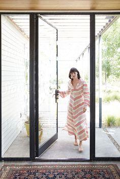 Woman walking into entrance of modern design home in Sonoma, California