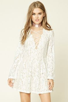 A fit and flare dress crafted from semi-sheer floral lace with a contrast lining, a lace-up plunging V-neckline, long bell sleeves, and an invisible back zipper.