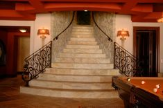 Man cave took on a literal meaning with this beautiful basement entertainment room and the staircase provides a grand entrance to it!  Carved Stone Creations design and installed this beautiful staircase which features rockfaced stone veneer on the walls and a complimentary mix of Travertine stone stair treads and flooring.  Click on the image to see other staircase projects by Carved Stone Creations.