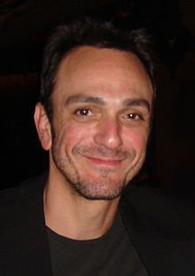 Head shot of broadly smiling man in black with receding dark hair and a days beard growth on his face.