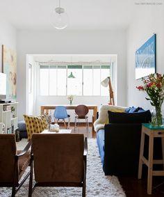 Sala de estar iluminada com sofá azul marinho, móveis de madeira e almofadas coloridas.