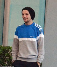 All smiles:Louis Tomlinson looked happy to be back on home turf when he landed at Heathow airport on Monday