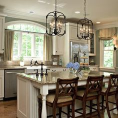 Traditional kitchen with painted white cabinets, a large kitchen island with room for 3 barstools, built in bench for the breakfast nook and desk with cork bulletin board.