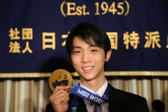 Sochi Winter Olympics men's figure skating gold medalist Yuzuru Hanyu shows his gold medal during a press conference at the Foreign Correspo...