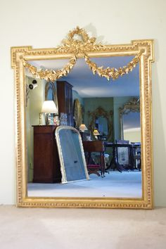 19th century French gilt Louis XVI style wall mirror. Decorated with ribbon tied flower garlands, laurel leaves and flaming torch and quiver of arrows. Lovely oil and water gilding. The mirror plate is in very good condition with some spotting. There is some wear to the gilding at the base.