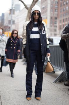 A varsity jacket paired with wide-leg jeans and a beanie.