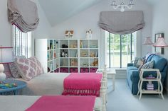 Pink and blue shared girls' room boasts white 4 poster twin beds dressed in hot pink fringe throw blankets flanking a round blue bedside table.