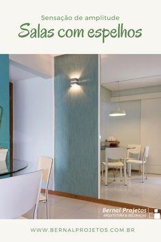 A sala do pequeno apê tem parede revestida de espelho, que junto com as cores claras e a decoração clean criam a sensação de maior espaço. Projeto da Bernal Projetos Mirror, Lighting, Furniture, Home Decor, Mirrored Wallpaper, Wall Papers, Tiffany Blue Walls, Side Wall, Apartments