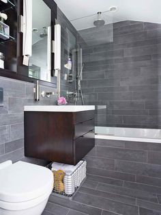 Contemporary bathroom tiles can make all the difference in your bathroom makeover. In this small space, gray, horizontal tiles work to add subtle visual interest and make the space feel larger. Stylish Bathroom, Bathroom Makeover, Small Bathroom, Grey Bathroom Tiles, Modern Bathroom, Bathroom Decor, Wood Bathroom Vanity, Grey Bathrooms, Upscale Bathroom