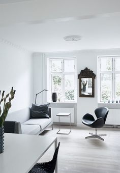 This living room is furnished with a Swan Chair from Fritz Hansen, couch from Paustian and a small coffee table from Flex Form.