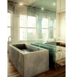 Integrado ao quarto, este ambiente apostou em banheira de cimento queimado para conferir ares indutriais ao espaço