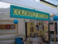 Colorfly Studio Sign - Love the colors in this booth sign.  Plus nice use of frames with screens (Are they screen doors? I can't tell) for hanging small pictures.