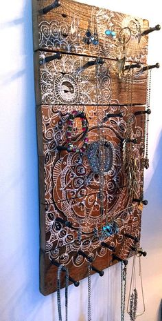 This is a large jewelry holder that I made out of wood from an old fence that we took down in the backyard. The wood is very rustic and I have painted it with my mandala doodles.