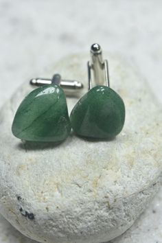 Handmade custom tumbled green aventurine stone cufflinks. The silver cufflinks are made with green aventurine stones, that have wonderful vibrant coloring. The cuff links are hand made in the USA. It comes from a smoke free environment. The green aventurine cufflinks measure:  23 mm x 16 mm x 7 mm  or .9 inches x .63 inches x .29 inches.  Please note: These are not identical. While the stones are selected due to their similar shape, color and texture there are some minor differences, that…