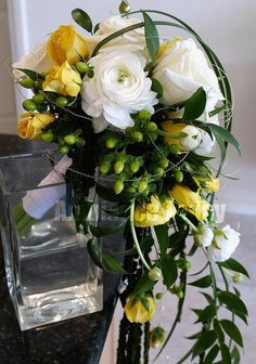 #ranunculus, #spray roses,  #hypericum, #Italian ruscus, #lily grass and  silver bullion wire in a #cascade bouquet    Photo by Bas Schweitzer