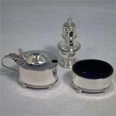 A Sterling Silver three-piece condiment set, in a very plain oval Georgian style, and consisting of a pepper pot, open salt cellar, and covered mustard pot, the latter two items with original blue glass liners, and sitting on four cushion feet, the pepper pot with a pull-off lid with finial. Made by the Adie Brothers of Birmingham in 1939. The dimensions of this fine hand-made silver condiment service are height of pepper pots 7.5 cms (3 inches), length of mustard pot 7.5 cms (3 inches), and…