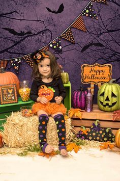 cute Halloween setup: backdrop of black bats & tree branches against a purple sky ~ hay bale or apple crate for seating ~ faux leaves & pumpkins for props