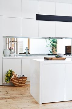 """The kitchen underwent a complete transformation with old cabinetry removed and replaced and plenty of bench space and storage added. """"My style is very clean and fresh,"""" says Penny. To break up the expanse of white a long black suspended light from [Light Project](http://lightproject.com.au/