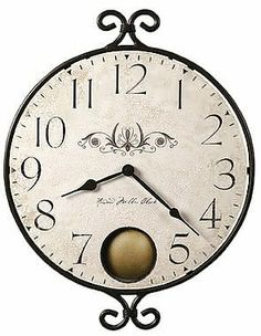 The Howard Miller Randall Wall Clock features a charming vintage-inspired design with warm grey wrought iron frame. A peep hole at the six position gives a view of the interior antique brass pendulum.