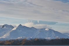 A plume rises from Bogoslof volcano, partially obscured by a mountain on Unalaska Island, in this view from Unalaska, about 60 miles east of the volcano, on Wednesday, Dec. 22, 2016. (Lynda Lybeck-Robinson / ADN reader submission)