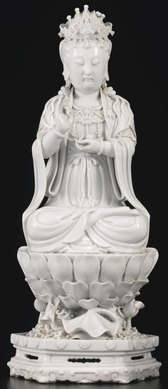 A DEHUA SEATED GUANYIN CHINA, QING DYNASTY, 19TH CENTURY shown seated in dhyanasana atop a large lotus blossom with overlapping petals, rising from swirling waves with further lotus stems bearing buds and large curling leaves, all supported on a hexagonal stepped base, the left hand holding an alms bowl, the right hand in vitarkamudra, the back impressed with a double-gourd seal reading Fujian Dehua, and a square seal reading Da Ming Wanli nian zhi  Height 17 1/4  in., 43.8 cm
