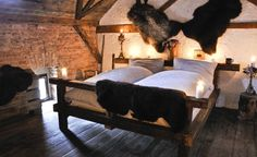 "Medieval Hotel Detenice. Prague. Authentic medieval hotel. (#24. ""Rooms are outfitted with furniture made from solid timber beams (as they would have been around the 13th century A.D.). Sheepskins and weaponry hang from the walls-but historical accuracy stops short of horsehair ticking in the mattresses. (Courtesy Medieval Hotel Detenice)"")"