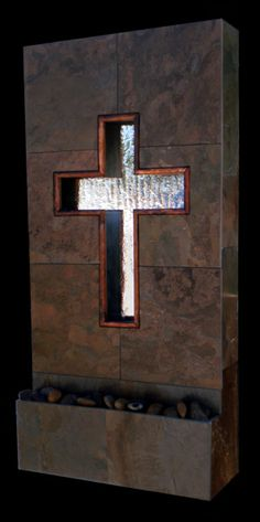 """The Sacrifice """"Crucifix of Jesus"""" wall fountain is framed in a multi color stone with a removable face that has a silhouette of cross delicately framed in hand torched copper."""
