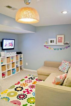 Playroom in blue with colorful accents.  Looks like a basement, but would work in our dining room converted to kids play room.