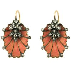 circa 1890.  A pair of antique earrings in the form of stylized shells with pink enamel and foliate diamond detailing, in silver and 18k. France.