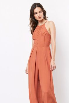 """Simply irresistible. This wide leg, open back jumpsuit is a statement piece with beauty only matched by it's comfort. Wear braless if you can, or with a bralette for extra support and coverage. Not wrinkle-resistant - must use a steamer.   Fabric: 65% Viscose 35% Rayon Color:Backed Clay, Rustic Orange Sizing: Standard Women's US Sizes Model in: Size S Model Measurements: Height 5'9"""", Waist 26"""", Bust 32B"""", Hips 32"""" Style:Wide leg jumper, open back jumpsuit Garment Care: DryClean…"""
